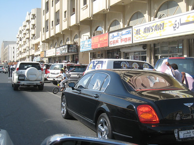 The row of car accessory shops who are flat out on National Day applying decals to cars. The pictures are printed on a thin perforated mesh similar to that used for advertising on the sides of buses.