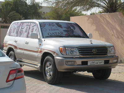 Its common for people in the Gulf to decorate their cars for their country's National Day. This Landcruiser is covered with pictures of the Qatar ruling family.