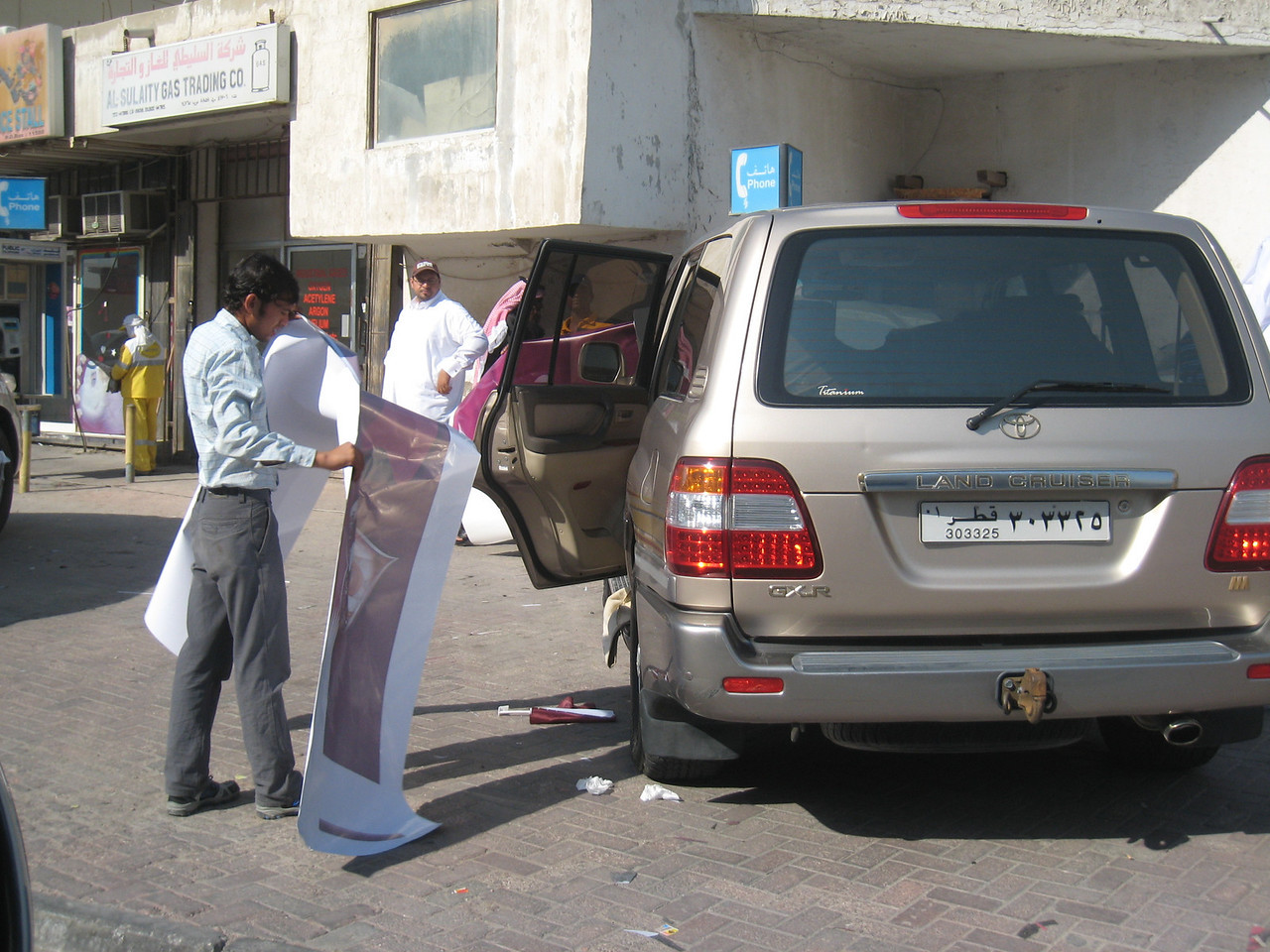 The choice of pictures has been made and a worker prepares to position the decal onto a car.