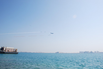 The Herc and accompanying jets trailing burgundy and white smoke, the colours of the Qatari flag.
