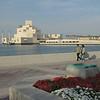 Strollers on the Corniche enjoy the Museum of Islamic Art in Doha, Qatar.