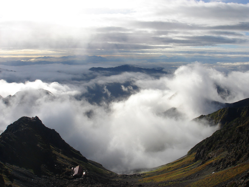 LOOKING DOWN TO SESSHO HUT FROM, YARI PEAK WITH FUJI JUST VISIBLE ON HORIZON (MIDDLE RIGHT).