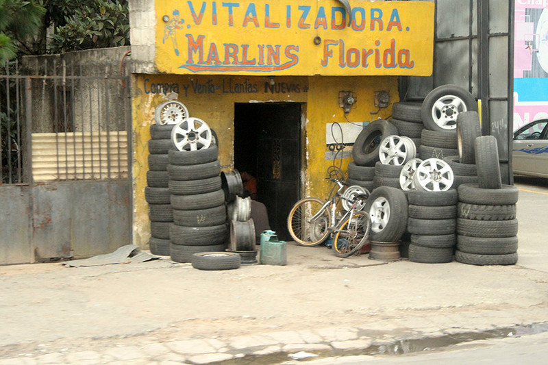 """When car owners in the US replace their """"worn out"""" tires with new ones, the old ones end up down here for sale in shops like this one."""