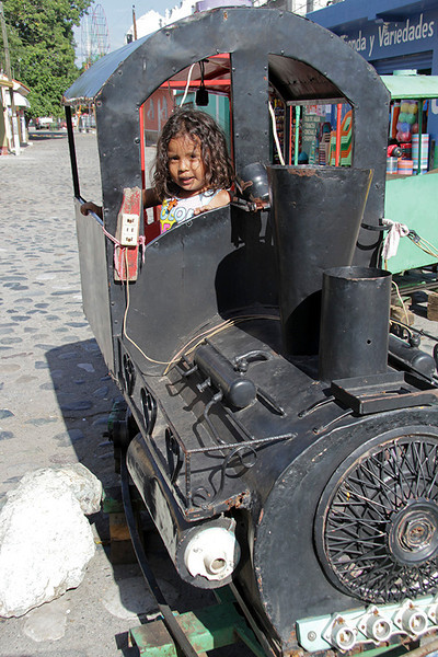 "Walking back from the church we met this adorable little girl who was ""driving"" the train."