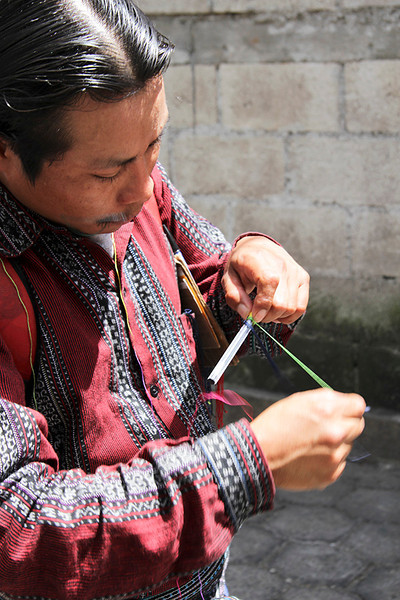 This artist was personalizing pens by weaving names into a fabric sheath for the pens.