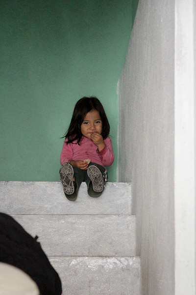 Nicolas's daughter watched quietly from the top of the steps. She will one day follow in her father's footsteps as religious leader of the Mayan believers.