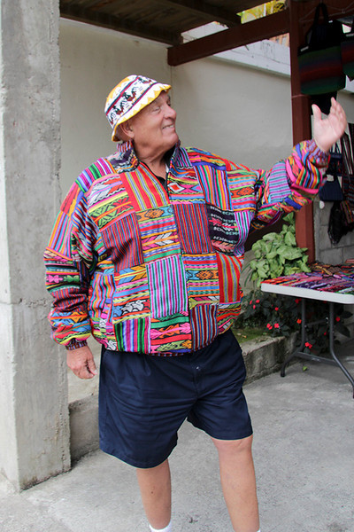 "John (in his ""chicken "" hat) models a colorful Mayan jacket he purchased."
