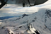 Small plane flying over snow covered Mount Rainier Washington