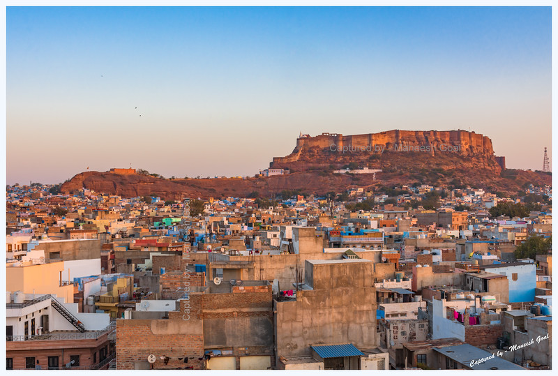 Blue city, Jodhpur, bathed in the golden light of sunrise. Mehrangarh Fort in the background.