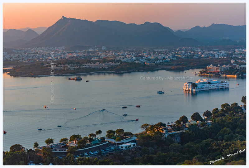 View of Lake Pichola, Udaipur, in the golden light of evening. Picture taken from Machla Magra hilltop near Dudh Talai. Sajjangarh Monsoon Palace can be seen in the top left-hand side of the picture.