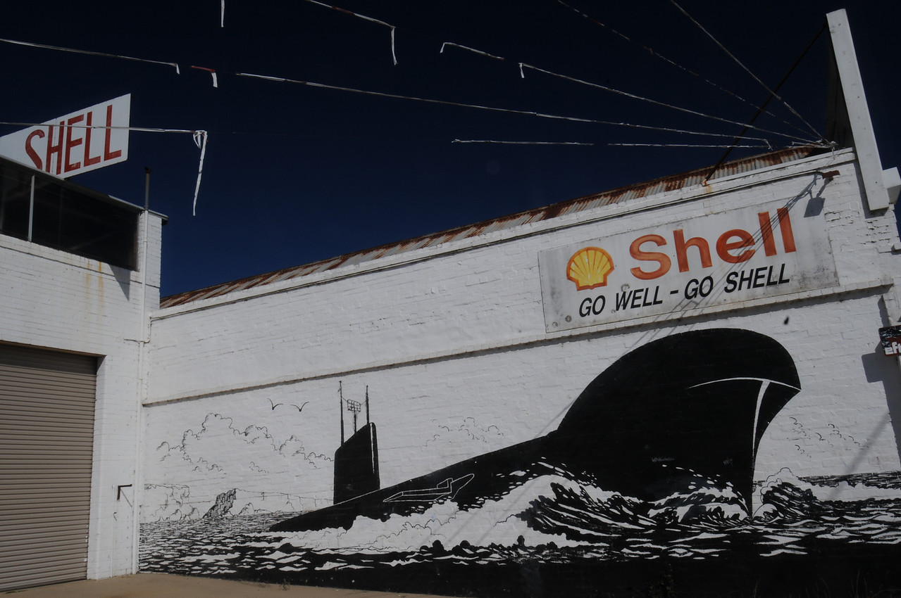 A mural on the side of the service station depicting the city's claim to fame.  That would be an old submarine they've partially buried off the road and turned into a tourist attraction.  Why here, in the middle of nowhere -and very far inland- I'm not sure.