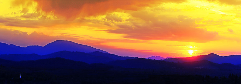 This image is cropped from the full panorama version. A spectacular sunset hangs over Shasta Bally and the mountains west of Redding, CA. The white steeple of a church stands out in the foreground.