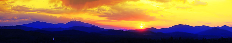 A spectacular sunset hangs over Shasta Bally and the mountains west of Redding, CA. The white steeple of a church stands out in the foreground. This panoramic image may be enlarged up to 10 feet wide to add drama to any room.