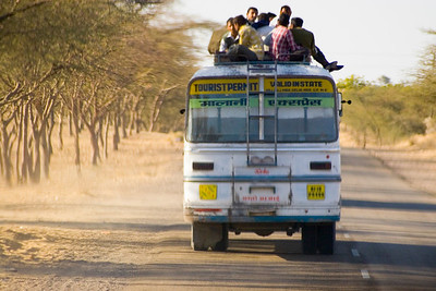 A crowded bus is no challenge for these guys.  They catch a lift on the top.  This is a common scene throughout India.