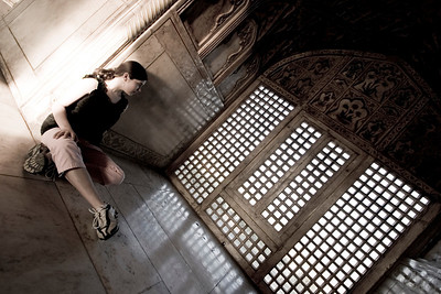 Shahnaz gazes at a nearby river through the marble lattice-work from within the Red Fort of Agra.