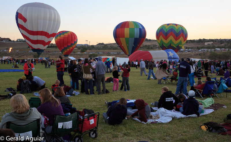 This photo was taken just before sunrise.  You can begin to appreciate the number of people attending the event and also see some of the hot air balloons getting ready for take off.   They use cold air fans to inflate the balloons while they are on their side.  Once inflated the helium burners are started to bring each balloon to the upright position.