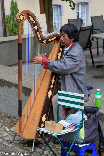 I really like the concentration and intensity of this harp player we found playing along the street.  Notice the different colored strings on his harp.