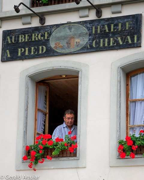 A gentleman checking out the street below in Gruyere.