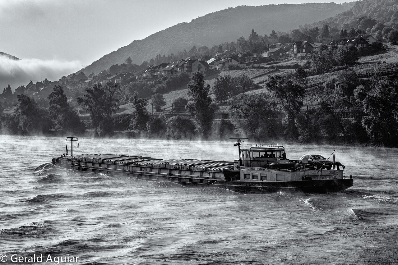 A barge battles with the Rhine River currents and winds