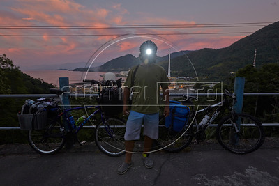 Dado Galdieri wears a head-lamp light during a brief stop to view of the Angra Nuclear power plant in Angra dos Reis, Rio state, Brazil, just off the Rio-Santos highway. The 500 plus kilometer road runs along the Atlantic Ocean, passing through, near and around dozens of beaches, waterfalls, mountains and forest - and a nuclear power plant. It is arguably of of Brazil's most beautiful roads. (Australfoto/Douglas Engle)