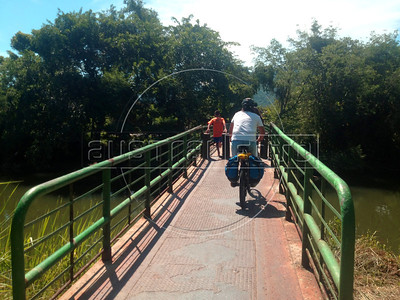 Dado Galdieri rides across a bike/pedestrian bridge in Monsuaba, near Angra dos Reis, Rio state, Brazil, during a trip on the Rio-Santos highway. The 500 plus kilometer road runs along the Atlantic Ocean, passing through, near and around dozens of beaches, waterfalls, mountains and forest. It is arguably of of Brazil's most beautiful roads. (Australfoto/Douglas Engle)