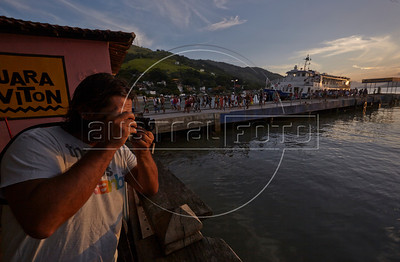 Dado Galdieri makes photographs as passengers disembark from the ferry arriving from Ilha Grande in Mangaratiba, Rio state, Brazil, just off the Rio-Santos highway. The island makes for a great escape from Rio, but in order to catch the 8am boat to the island, passengers must take a 5am bus from Rio. (Australfoto/Douglas Engle)