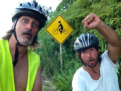 Douglas Engle and Dado Galdieri pose in front of a sign during a bicycle trip on the Rio-Santos highway. The 500 plus kilometer road runs along the Atlantic Ocean, passing through, near and around dozens of beaches, waterfalls, mountains and forest. It is arguably of of Brazil's most beautiful roads. (Australfoto/Douglas Engle)
