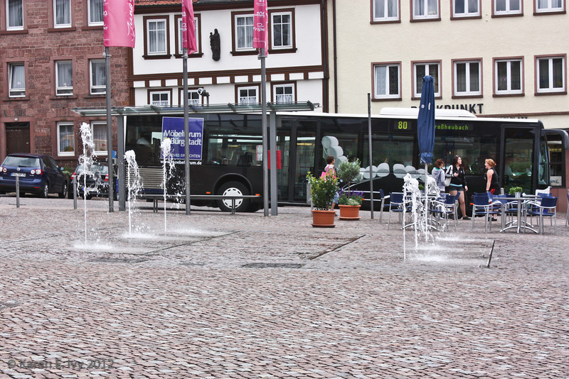 In a medieval town, a very modern street fountain - and a bus