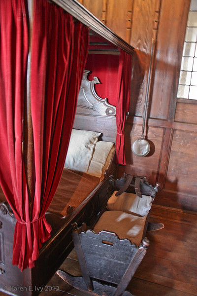Cradle and bed, ladies' chamber.  Note the warming pan on the wall.