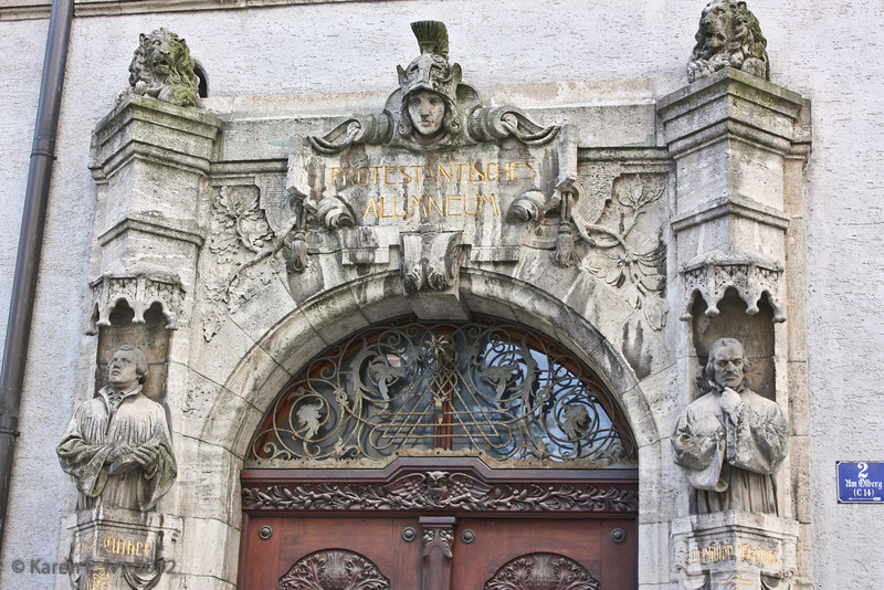 """Old portal. The sign says """"Protestantisches Alumneum"""". The word """"Alumneum"""" was used for Protestant religious schools that emerged out of former monasteries. This building still houses a religious fellowship."""