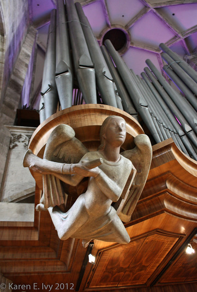 Upper organ base supported by modern carved angel