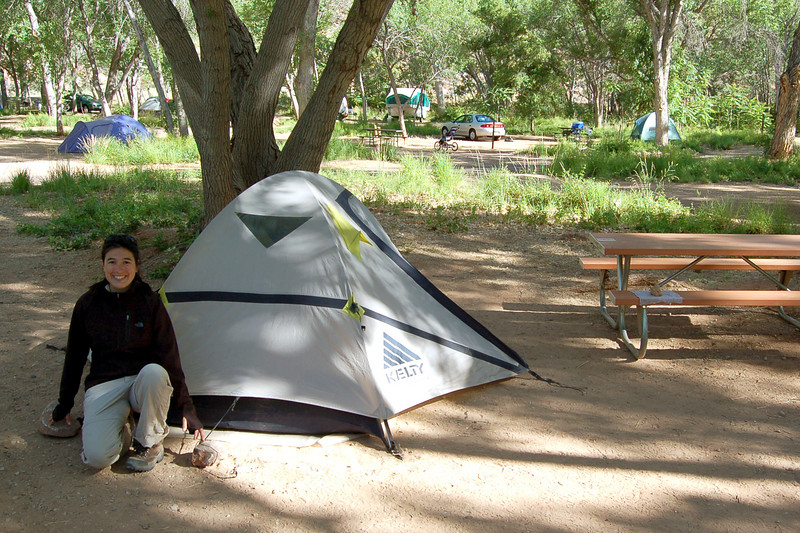 Michelle and our tent that is tied down with rocks because we destroyed our tent stakes trying to pound them into the rocky parking lot that is South Camground in Zion National Park, UT.