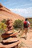 Michelle passing a rock cairn (trail marker) in Arches National Park, UT.
