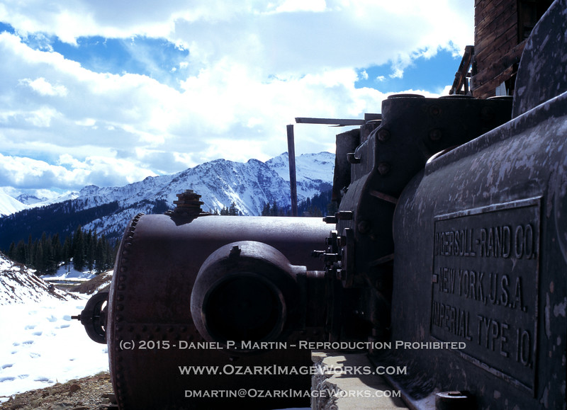 "September, 2006 - Abandoned mining operation near US-590 between Silverton and Ouray, Colorado. <br /> <br /> This is an Ingersoll-Rand ""Imperial Type 10"" steam-driven air compressor. Actually, it's several tons of 1912-vintage cast iron left behind whenever the mine operator gave up. This thing was huge -- those are full-grown pines in the background; the size 15 hiking boot tracks in the snow are mine.<br /> <br /> Nutsy-boltsy engineering info here: <br /> <br /> <a href=""http://www.practicalmachinist.com/vb/antique-machinery-history/ingersoll-rand-type-10-compressor-what-204113/"">http://www.practicalmachinist.com/vb/antique-machinery-history/ingersoll-rand-type-10-compressor-what-204113/</a><br /> <br /> ...check the post dated 05-12-2010 - 05:49 PM from ""hendeyman"". Anything big enough to use 36"" to 45"" flywheels deserves respect."
