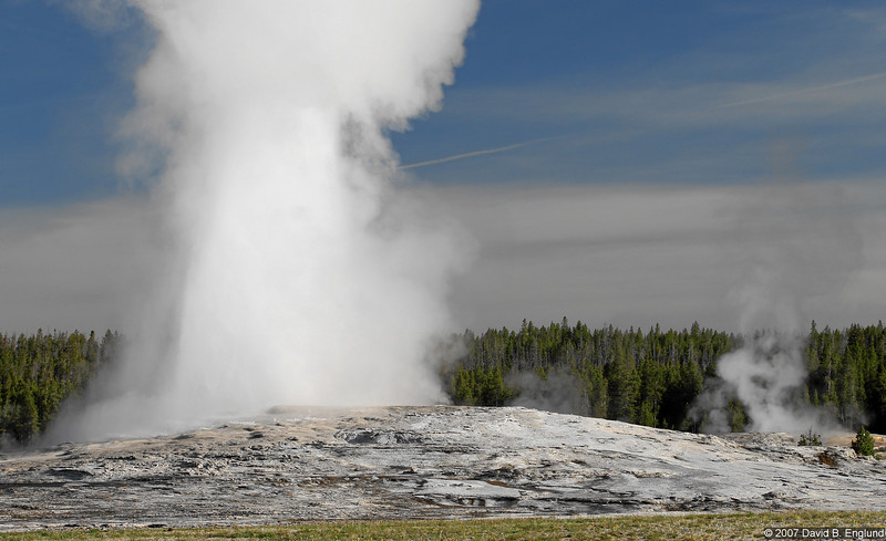 """Old Faithful begins to erupt.   There's a story that goes along with this shot. Some of my co-workers back home caught a bit of my excitement about visiting Yellowstone when viewing the <a href=""""http://www.nps.gov/archive/yell/oldfaithfulcam.htm"""">Old Faithful webcam</a>. We agreed that I would be at Old Faithful at 7:45 am on the morning of June 13 so I could turn and wave to them. Well, I was at Old Faithful with time to spare, but finding the webcam was another matter. Fortunately, I did find the webcam and positioned myself accordingly. There I was, facing the webcam at 7:45am (with my back to Old Faithful) when at 7:46 the famous geyser blew! I quickly turned and got off a couple of shots. The next two images tell the story better than words!"""