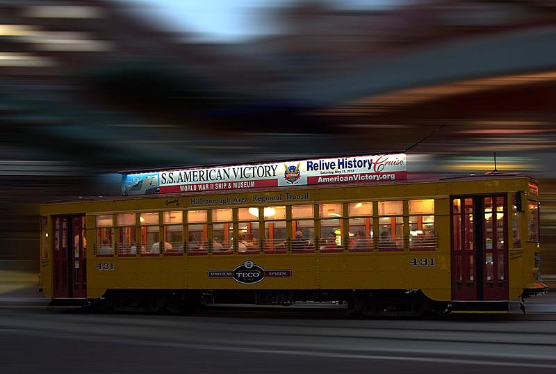 "331 As darkness falls, a TECO streetcar passes through central Ybor City, called ""Centro Ybor."""
