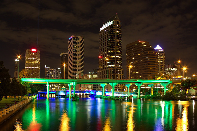 365 After dark the bus took us to the Platt Street bridge in Tampa, from which we took nighttime photos of downtown Tampa. The bridges in the photo are bathed in colored lights that change color over time. The two green bridges in the foreground are the Lee Roy Selmon (Crosstown) Expressway (FL 618), a toll road. The blue and purple bridge beyond the expressway is the Brorein St. drawbridge.