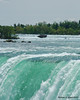 Water cresting over the Horseshoe Falls with an old barge stranded upstream