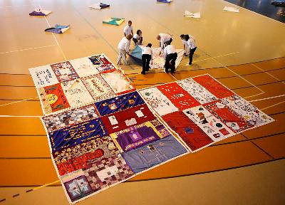 Volunteers unfurl one of the 1,900 quilt panels, featuring 4,500 names of people who have died of the disease, as part of the AIDS Memorial Quilt exhibition at the Rockland Community College field house Oct. 22, 2009.  The exhibit is on display until Saturday. ( Mark Vergari / The Journal News )