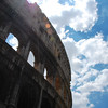 Colosseum with sun flare and clouds.