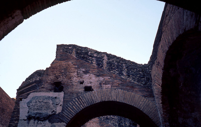 "Raw concrete covered with brick. The holes are from anchors to hold the stone to the facade. The brick arches were built to be self-supporting structure, with the concrete for the rest of the wall poured in after the brick ""forms"" were in place."