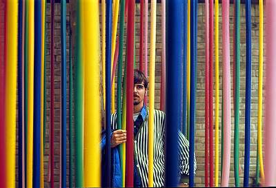 October 9th-11th, 1970 / Venice trip: Tim Redman's shot of me posing behind colored hoses hanging outside a pavilion at Venice's modern art fair.