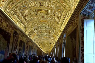 """Inside the Vatican museum.  Each Pope added on a wing to the Vatican's """"art collection""""  This one was called the Map room because the walls were adorned with maps of various parts of the world.  The ceiling was the most interesting part.  All of that is  hand done and insanly detailed with raised stone carved moldings around each image.  there's another picture in my photo gallery of Rome that shows an up close of this ceiling detail."""