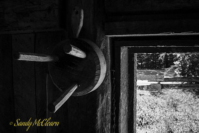 Milking stool hangs on the wall of a barn next to a window. Ross Farm Museum, Nova Scotia.