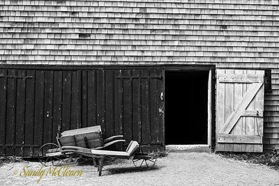 Two old wheelbarrows sit next to the open door of a barn. Ross Farm Museum, Nova Scotia.