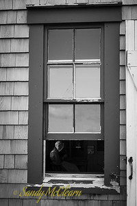 Woman in period dress seen through the open window of a one room school house. Ross Farm Museum, Nova Scotia.