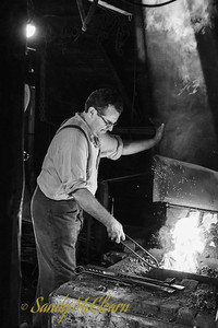 Blacksmith working the forge in his shop. Ross Farm Museum, Nova Scotia.