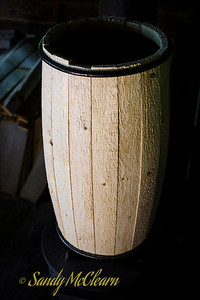 A barrel in the midst of the crafting process sits on top of a wood stove. Ross Farm Museum, Nova Scotia.