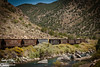 The Arkansas river running along Colorado Highway 50 along a nearly 30 miles long winding canyon just west of Canon City.  This happens to include some parked rail cars.