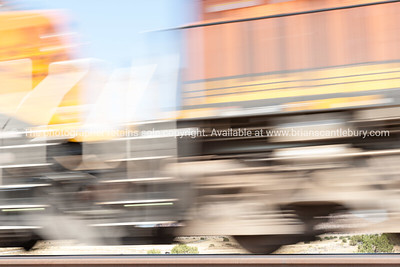 Mile long trains rumble through the New Mexico landscape alongside Historic Route 66, New Mexico, USA. Motion blur conveys the speed and movement.